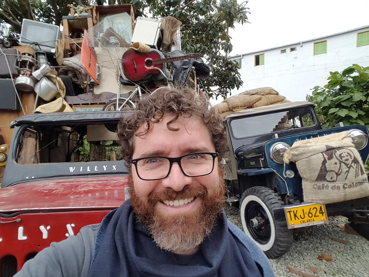 Photo of Francisco Posada standing in front of vehicles, stacked high with items, with Colombian license plates.